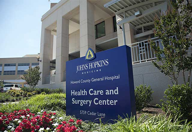 Johns Hopkins Medicine Howard County General Hospital Health Care and Surgery Center sign in front of entrance.