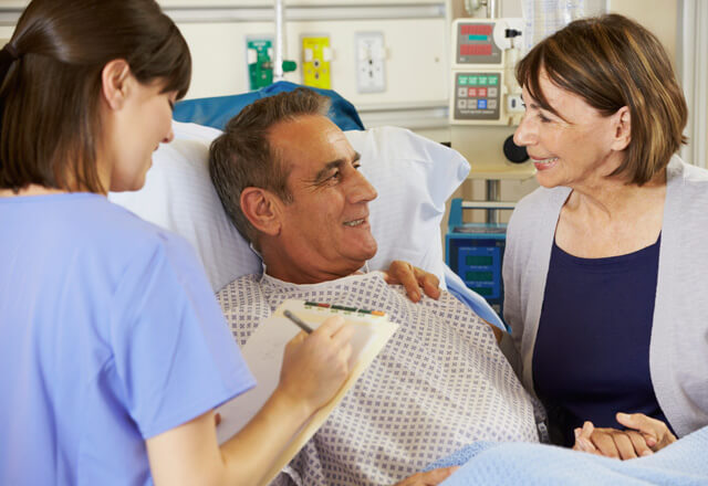Man in hospital bed smiling at wife