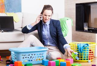 woman in work clothes surrounded by laundry basket and children's toys