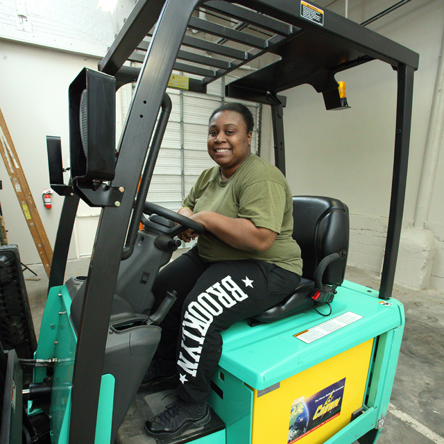 The photo shows Jessica Waters on a forklift.