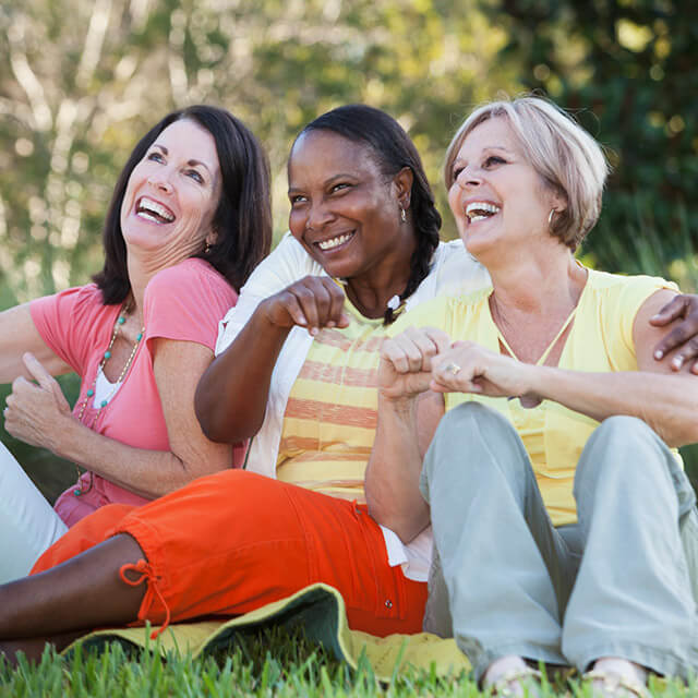 Three women sitting together outdoors