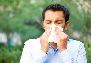 Man sneezing outdoors and covering his nose