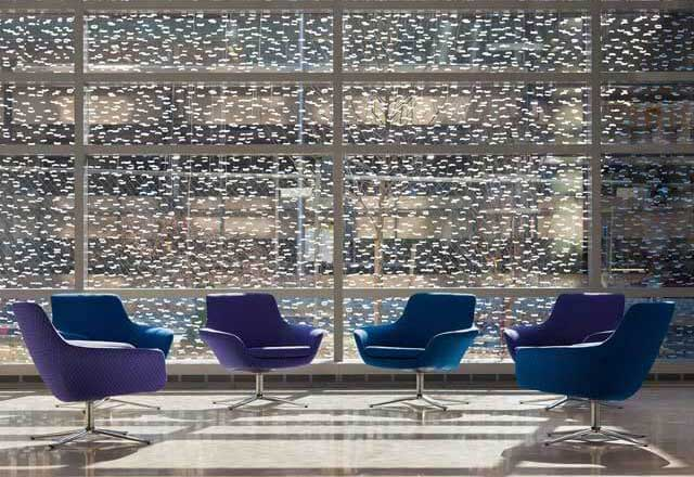 a seating area with a patterned window behind it