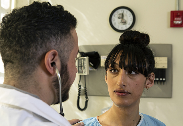 A transgender woman speaks with a doctor.