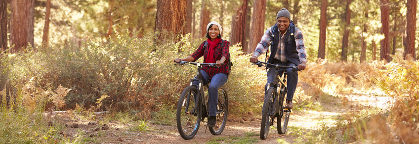 Healthy couple riding bikes through a wooded trail.