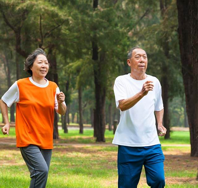 Older couple jogging on a wooded trail