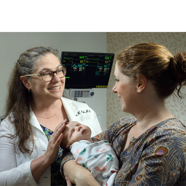 Neonatologist Susan Aucott with a young patient and mom.