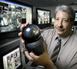 Ken Nyczaj holds a pan-tilt-zoom camera, the type that serves as the eyes for Corporate Security around campus.