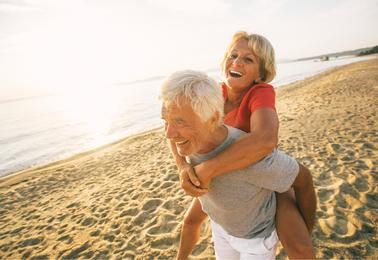 older couple piggy back ride on beach