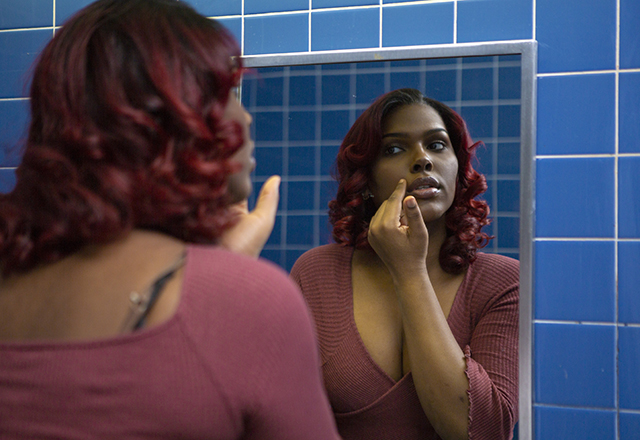 A young transgender woman looks at her face in the bathroom mirror.