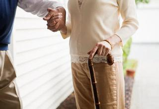 elderly woman with cane and helping hand