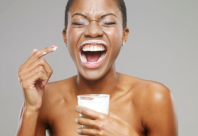 woman holding glass of milk with milk around her lips