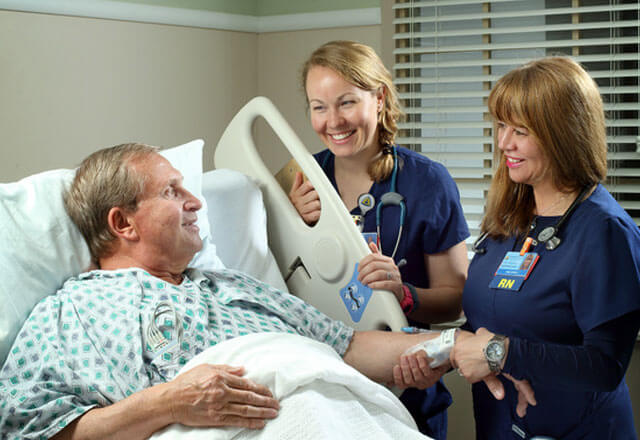 Photo of nurse providing bedside assistance to patient.