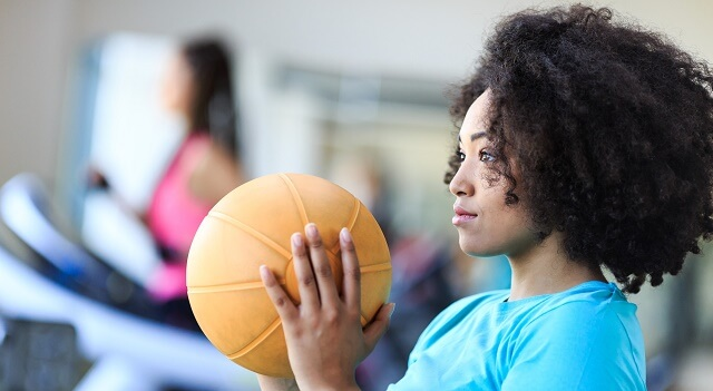 Young woman working out at gym with medicine ball