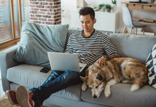 man on the sofa with his dog while having a televisit with his doctor