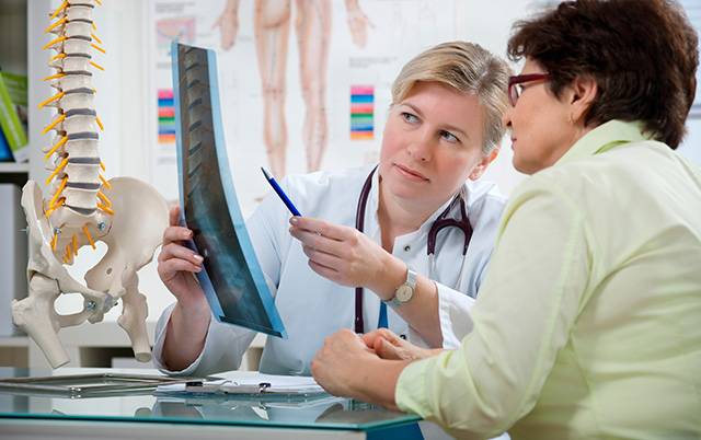 doctor patient looking at spine xray and model