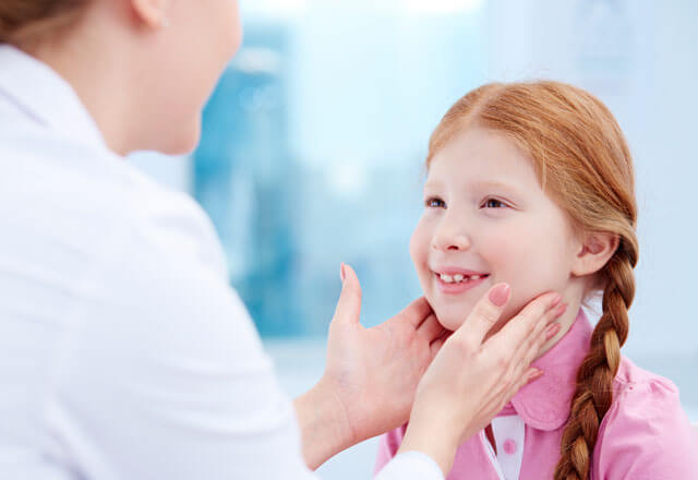 pediatrician checks glands on the neck of a child for swelling
