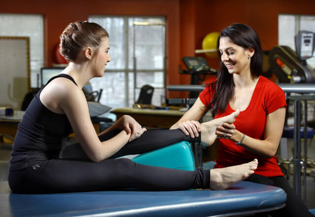a physical therapist working with a dancer