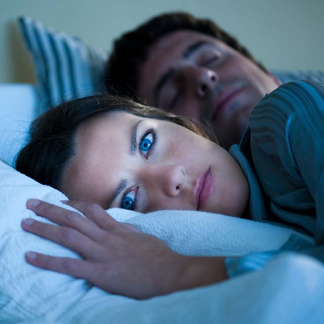 woman laying in bed who can't sleep