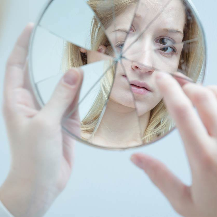 Girl looking at her reflection in a broken mirror