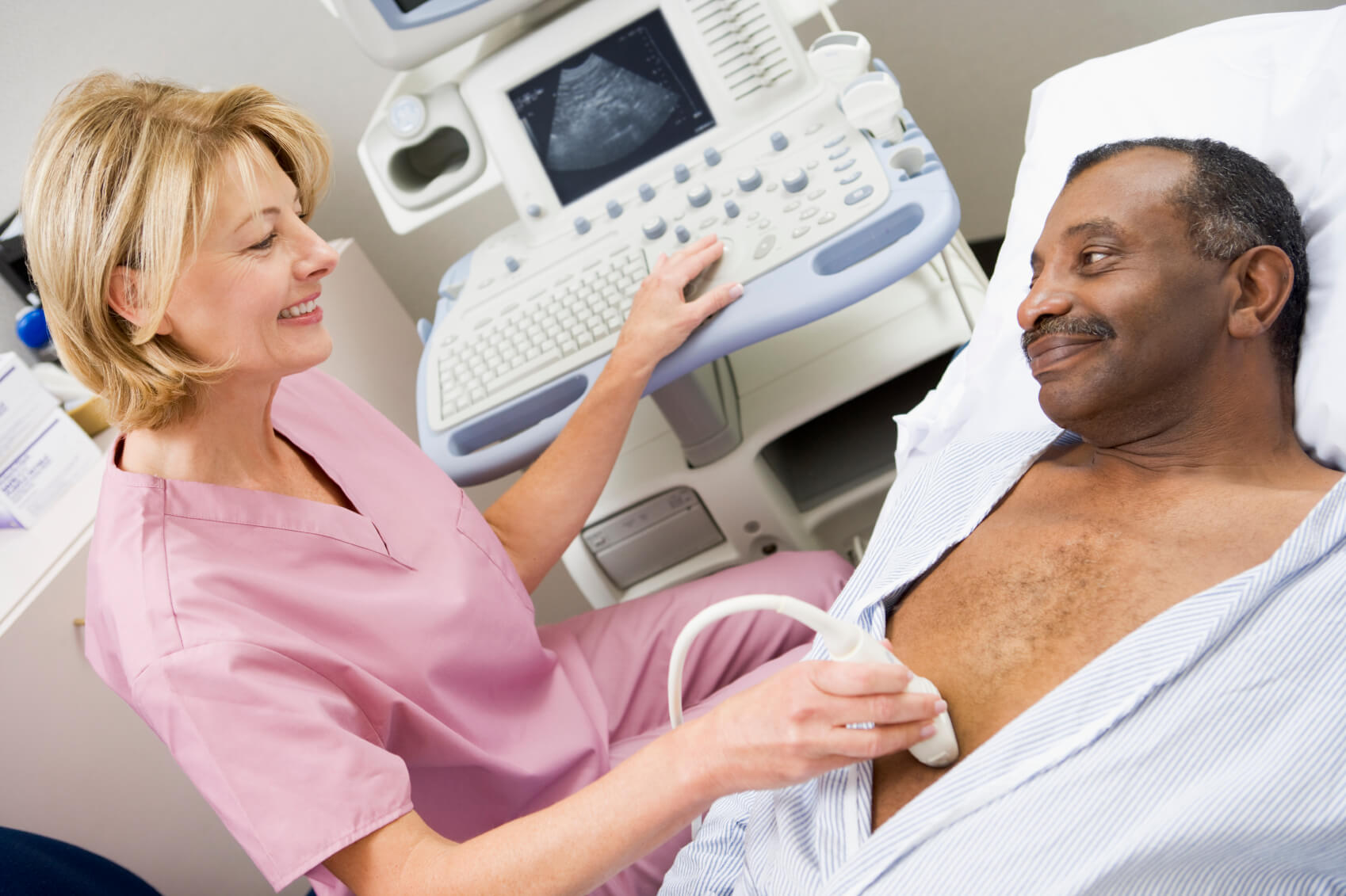 Radiology technologist preparing patient for ultrasound