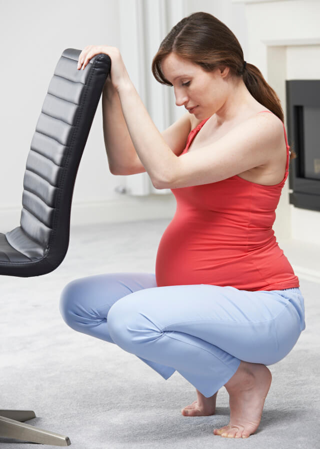 A pregnant woman stretching on a chair