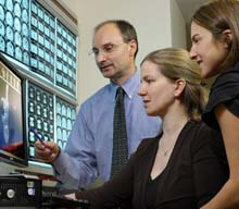 Dr. David Tunkel, Dr. Margaret Skinner and Dr. Emily Boss look at and discuss a patient's MRI.