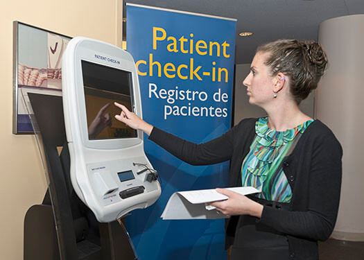 Woman checking in at kiosk at Pain Treatment Center