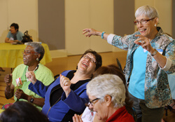 Marti Bailey, right, shares a laugh with Club Memory patients as they reminisce.