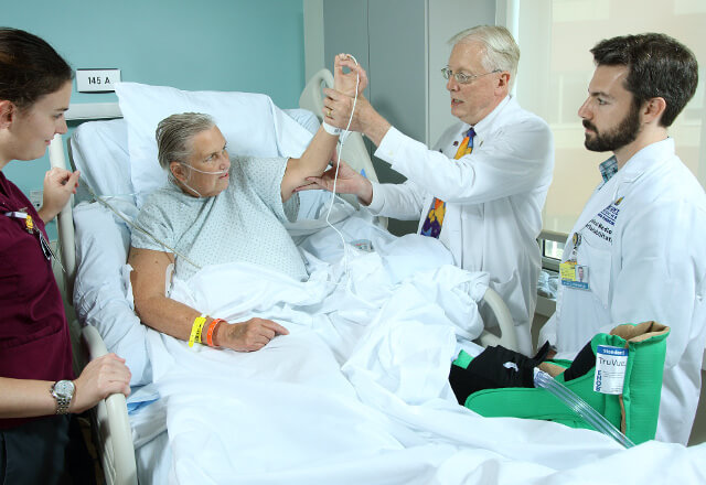 Dr. Stiers examining a patient with his team
