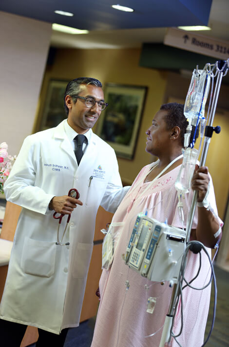 Hospitalist Anirudh Sridharan checks in with patient Katherine Clarke, admitted to Howard County General Hospital for a pulmonary embolism.