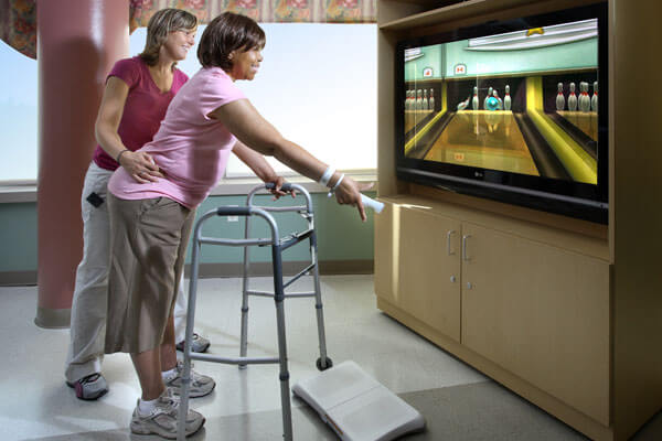 Middle-aged, rehabilitation patient playing Nintendo Wii