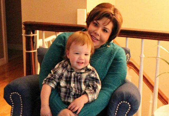 Ashley, a former gynecologic oncology patient, and her son sitting in a chair.