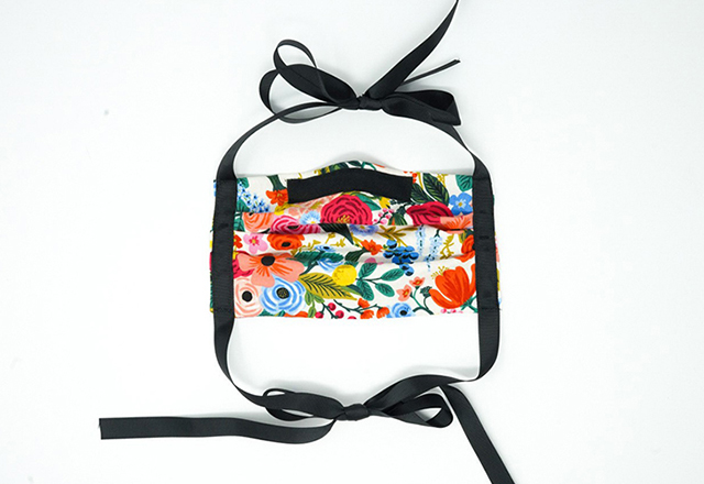 A handsewn mask in a colorful floral print.