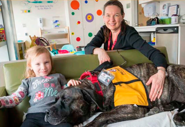 volunteer with child and service dog
