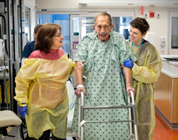 Nathan Maryn, a 76-year-old patient recovering from surgery to remove several soft tissue tumors, walks with the aid of his wife, Barbra, and physical therapist Jennifer Sahm (right). Studies show that getting patients—even the critically ill—up and out o