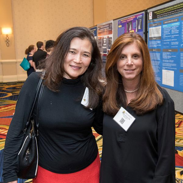 Photos shows Yoshimi Anzai, associate chief medical quality officer at University of Utah Health Care, and conference organizer Pamela Johnson, vice chair of quality and safety in radiology at Johns Hopkins University School of Medicine, discussing improvements and innovations during the poster session.