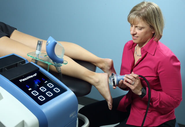 A physical therapist using shock wave therapy on a patient's foot