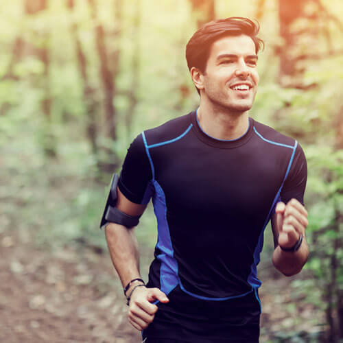 Man running through a wooded trail
