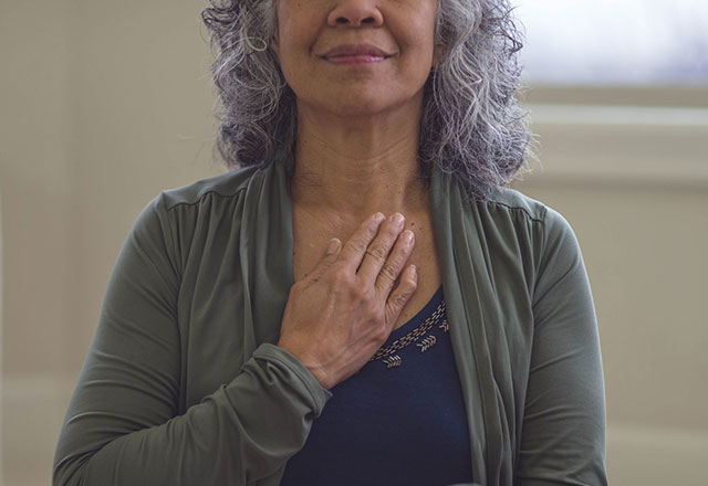 An older woman doing deep breathing exercises
