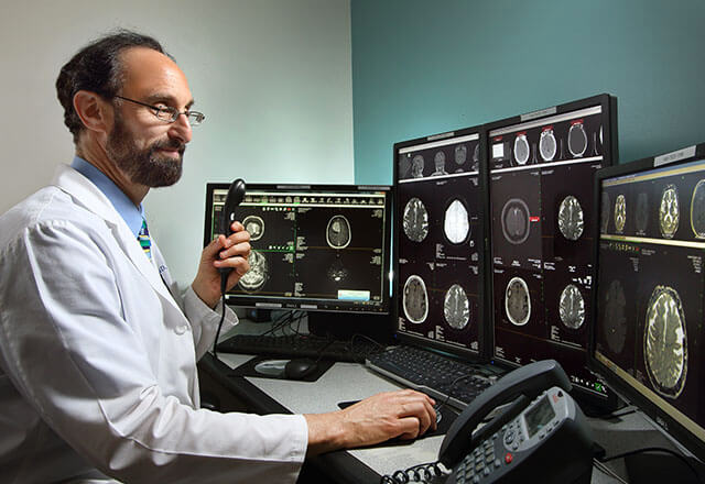 Neuroradiologist reading brain MRI images.