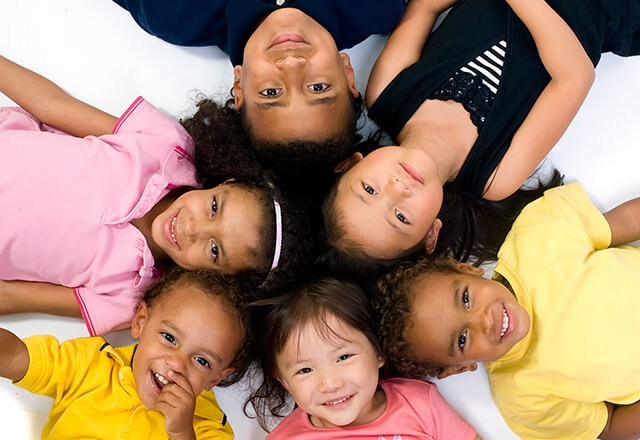 A group of children, diverse in race, laying in a circle