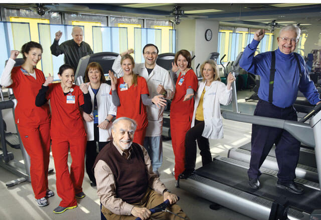 Cardiac rehab nurses and physicians stand in the rehab room with patients on treadmills