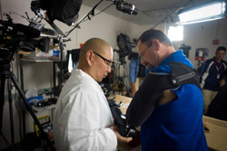 Albert Chi observes as Johnny Matheny practices thought-controlled robotic motion with his new bionic arm. The mechanical limb, perfected by the Johns Hopkins Applied Physics Lab, is considered the most sophisticated arm ever made and weighs about as much