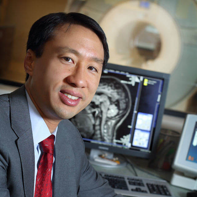 Dr. Frank Lin sitting beside an MRI machine.