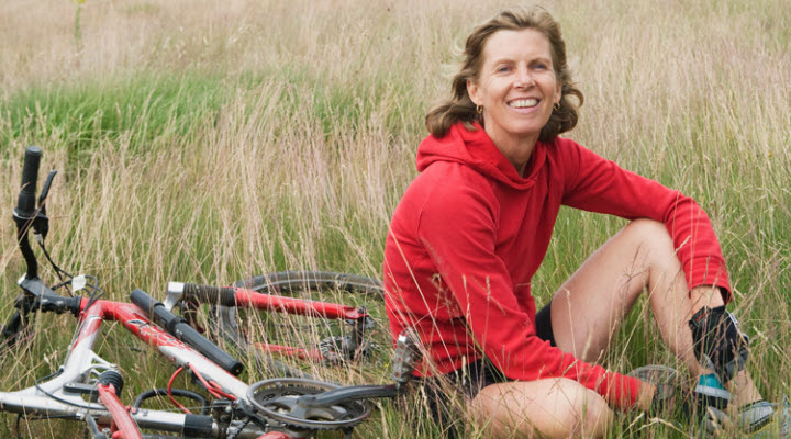 woman sitting in a field next to her bike