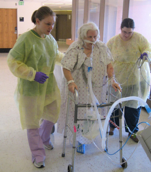 a provider helping a hospital patient with a walker