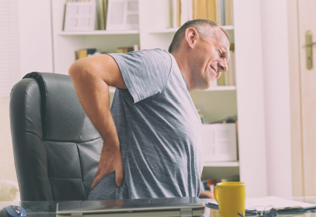 A man touching his lower back in pain