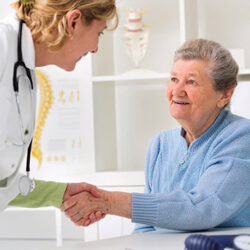 Female care provider shaking hands with elderly female patient