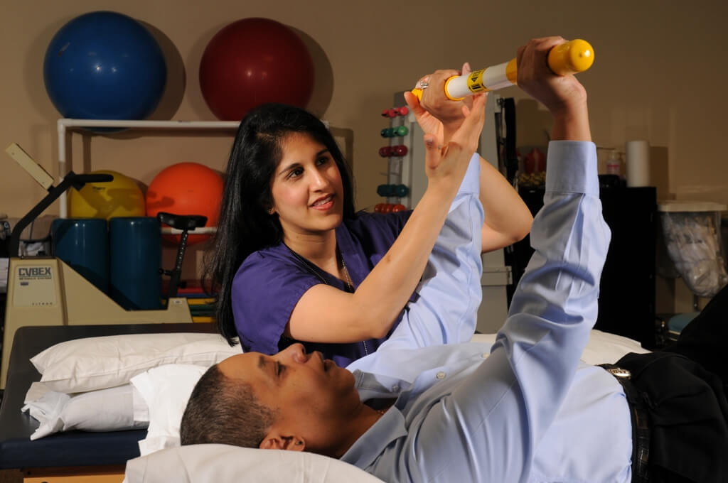 Outpatient Rehab Specialist works with a patient
